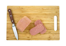 Luncheon meat sliced on cutting board Royalty Free Stock Image