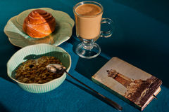 Luncheon shooted in sunny morning with a vintage notepad. Light breakfast of muesli, cinnamon roll and coffee shooted in sunny morning royalty free stock image