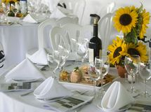 Luncheon Table. Stock photo of an elegant table set for a luncheon in the country.  There is a vase of sunflowers for a centerpiece, a bottle of wine and an Stock Image