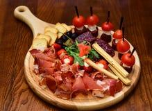 Lunchkött på träuppläggningsfatet Matmagasin med läcker skivad skinka och canape med tomater, begrepp för lunchkött Äta och arkivbild