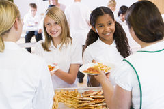Lunchladies serving plates of lunch in a school Royalty Free Stock Photos
