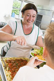 Lunchlady serving plate of lunch in a school royalty free stock images