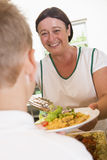 Lunchlady serving plate of lunch in a school stock photography