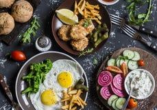 Lunchtabell - stekte ägg, fiskbollar, potatischiper, grönsaker, såser, hemlagat bröd på en mörk bakgrund royaltyfri fotografi