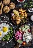 Lunchtabell - stekte ägg, fiskköttbullar, potatischiper, grönsaker, såser, hemlagat bröd på en mörk bakgrund royaltyfria bilder