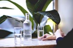 Lunchtid i stadsrestaurang eller kafé Rent vatten i en flaska, i exponeringsglas Houseplants near fönstret, dagsljus Royaltyfri Bild