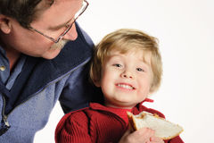 Lunchtime. Father smiling at son who is holding a peanut butter and jelly sandwich Royalty Free Stock Photos