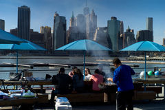Lunchtime BBQ in NYC. Against the backdrop of Downtown Manhattan, New Yorkers lunch on a BBQ on the marina at Brooklyn stock photos