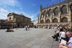 Lunchtime on a sunny day in Bath, England. Locals and tourists relax on benches and listen to buskers in a public square in Bath, England, outside the historic Royalty Free Stock Image