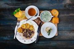 Lunchuppsättning Okroshka champinjon med hashbrowns och traditionell rysssallad, tjänade som på magasinet med besticket royaltyfri fotografi