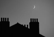 Lune au-dessus des dessus de toit photo libre de droits
