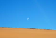 Lune au-dessus du désert Photographie stock