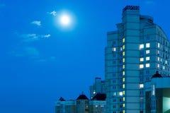 Lune dans le ciel nocturne au-dessus de la ville Photographie stock libre de droits