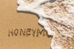 Lune de miel - inscription à la main sur le sable de mer lavé Image libre de droits