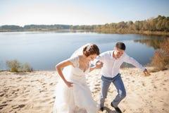 Lune de miel juste de marier épousant des couples jeune mariée heureuse, marié se tenant sur la plage, embrassant, souriant, rian Photographie stock libre de droits