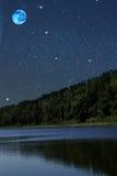 Lune en bois de nuit de lac Photographie stock