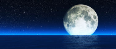 Lune en hausse au-dessus de mer Photos stock