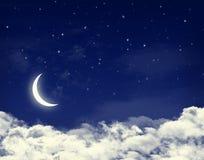 Lune et étoiles dans un ciel bleu de nuit nuageuse Images stock