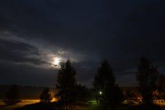 Lune la nuit sur le ciel nuageux Photographie stock libre de droits