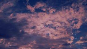 Lune rouge se levant dans les nuages gonflés rouge foncé dramatiques banque de vidéos