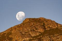 Lune se levant au-dessus de la montagne Image stock