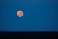 Lune se levant sur l'horizon Photos libres de droits