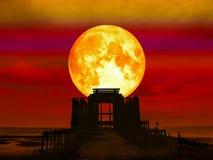 lune superbe de plein sang au-dessus de temple d'abandon en mer Photos stock