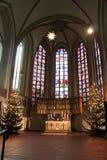 Luneburg, Германия - 10 12 2017: Алтар рождества в католической церкви и цветное стекло за им стоковые фотографии rf