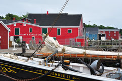 Lunenburg, Nova Scotia. Canada - July 23, 2009: Two familiar sights on the Lunenburg waterfront, the Bluenose II, and the seafood wholesaler Adams and Knickle Stock Image