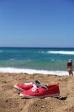 Lunettes de natation et sneakres rouges sur la belle plage Photos libres de droits