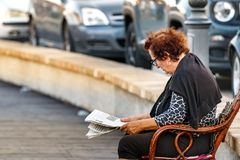 Lunettes de port d'une femme supérieure, lisant un journal se reposant sur une chaise en dehors du bord de mer de Rhodes, la Grèc photo stock