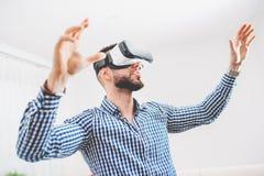 Lunettes de port de réalité virtuelle d'homme beau et barbu dans le studio coworking moderne de conception intérieure Smartphone  Images stock