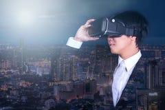 Lunettes de port de réalité virtuelle d'homme d'affaires et vue de ville de nuit images libres de droits
