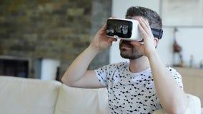 Lunettes de port de réalité virtuelle d'homme Tir de studio, divan blanc banque de vidéos