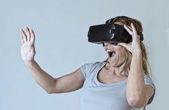Lunettes de port de vision de réalité virtuelle du casque VR de femme blonde attirante observant la vidéo Photographie stock