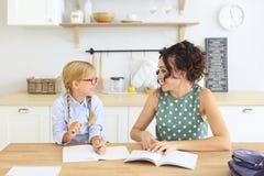 Lunettes de port de fille d'école d'ute de ¡ de Ð faisant des devoirs avec la mère à la maison photos stock