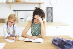 Lunettes de port de fille d'école d'ute de ¡ de Ð faisant des devoirs avec la mère à la maison image libre de droits