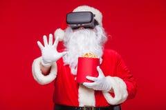 Lunettes de port de réalité virtuelle de Santa Claus et un seau rouge avec le maïs éclaté, sur un fond rouge Noël Photo libre de droits