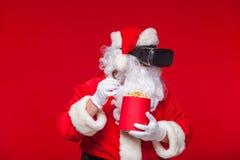Lunettes de port de réalité virtuelle de Santa Claus et un seau rouge avec le maïs éclaté, sur un fond rouge Noël Photos libres de droits