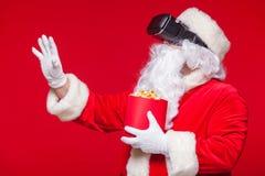 Lunettes de port de réalité virtuelle de Santa Claus et un seau rouge avec le maïs éclaté, sur un fond rouge Noël Photos stock