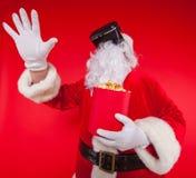 Lunettes de port de réalité virtuelle de Santa Claus et un seau rouge avec le maïs éclaté, sur un fond rouge Noël Images stock