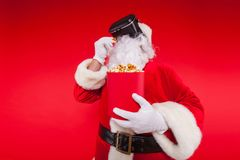 Lunettes de port de réalité virtuelle de Santa Claus et un seau rouge avec le maïs éclaté, sur un fond rouge Noël Photo stock
