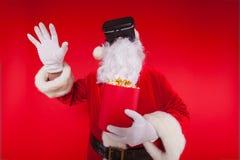 Lunettes de port de réalité virtuelle de Santa Claus et un seau rouge avec le maïs éclaté, sur un fond rouge Noël Photographie stock libre de droits