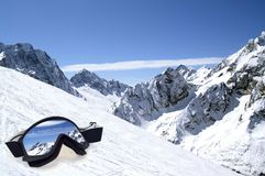 Lunettes de ski avec la réflexion des montagnes Photographie stock