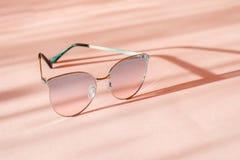 Lunettes de soleil élégantes modernes de cadre en métal sur le fond de papier rose à la mode au soleil Configuration plate vacanc photos stock
