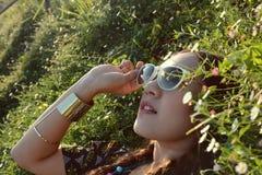 Lunettes de soleil asiatiques d'usage de femme se situant dans le jardin d'agrément Photographie stock libre de droits