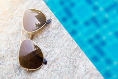 Lunettes de soleil avec la lumière naturelle sur le poolside photo stock