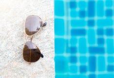 Lunettes de soleil avec la lumière naturelle sur le poolside photographie stock libre de droits