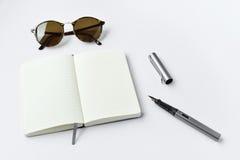 Lunettes de soleil, carnet, et stylo, sur le fond blanc Photographie stock libre de droits
