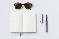 Lunettes de soleil, carnet, et stylo, sur le fond blanc Images stock